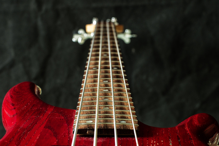 Red bass guitar with four strings on dark background