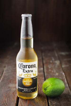 Editorial photo of Corona beer with lime on wooden background. Selective focus Editorial