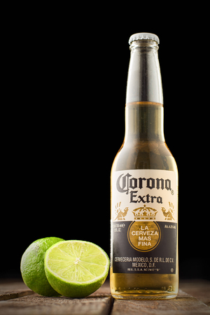 Editorial photo of Corona beer with lime on wooden table isolated on black. Copy space Redakční