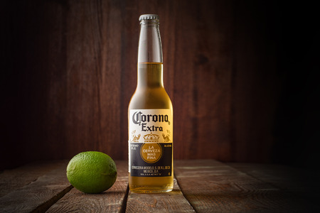 Corona beer with lime on dark wooden background with copy space
