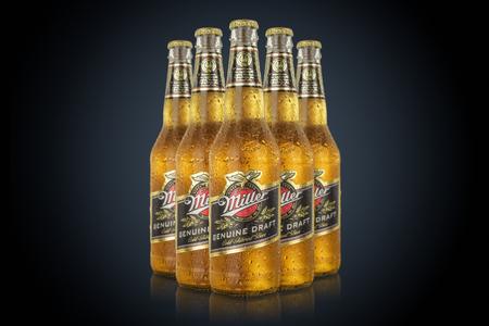 MINSK, BELARUS - JUNE 29, 2017:five bottles Miller Genuine Draft Beer isolated on black. Miller is the original cold filtered packaged draft beer.