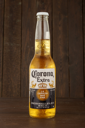 MINSK, BELARUS - JUNE 29, 2017:  bottle of Corona Extra beer on wooden background, one of the top-selling beers worldwide is a pale lager produced by Cerveceria Modelo in Mexico