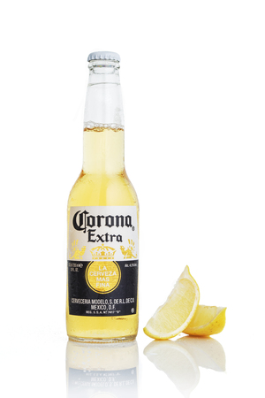 MINSK, BELARUS - JULY 10, 2017: bottle Corona Extra beer with lime isolated on white, one of the top-selling beers worldwide is a pale lager produced by Cerveceria Modelo in Mexico.