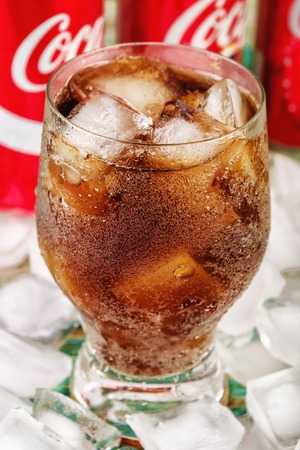 MINSK, BELARUS - JULY 09, 2017: Coca-cola glass with ice close-up and three Coca-Cola cans. Vertical photo. Coca-Cola is a carbonated soft drink popular all over the world.