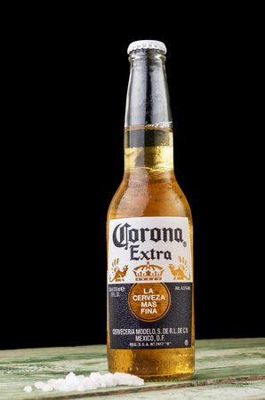 MINSK, BELARUS - JULY 10, 2017: Editorial photo of bottle of Corona Extra beer on wood background, one of the top-selling beers worldwide is a pale lager produced by Cerveceria Modelo in Mexico. Editorial
