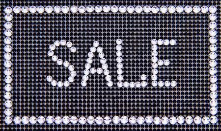 Word SALE is made rhinestones on a black canvas background