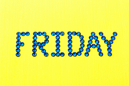 Word FRIDAY is made blue rhinestones on a yellow background