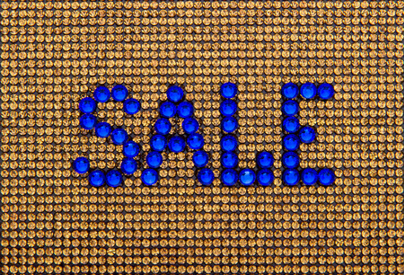 Word SALE is made rhinestones blue color on a gold canvas background Stock Photo