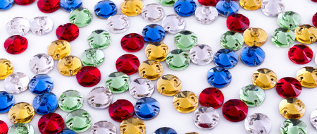 Colored round embroidered rhinestones on white background