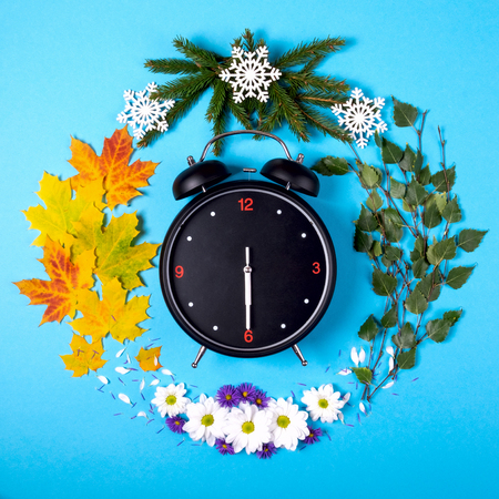 Representing the seasons of the year through the alarm clock and natural material on a blue background. Summer Top view