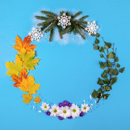 Wreath made of natural material, symbolizing the seasons of the year, on a blue background. Top view
