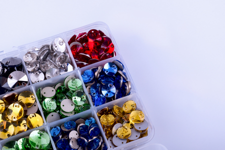 Bright colored rhinestones round shape in a box on a white background