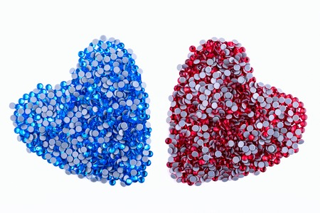 A lot of red and blue rhinestones made in the shape of a heart on a white background. Top view
