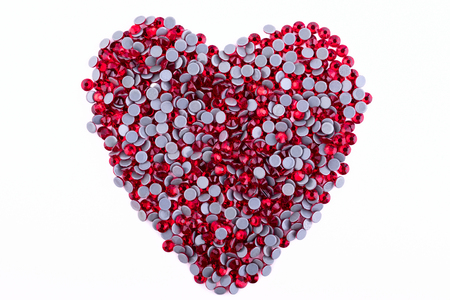 A lot of red rhinestones made in the shape of a heart on a white background. Top view Stock Photo