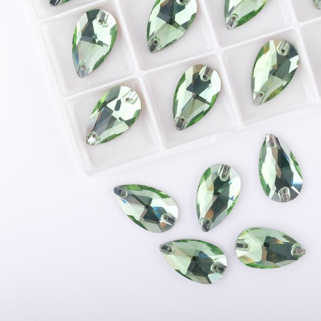 Precious stones green color in the pallet on a white background