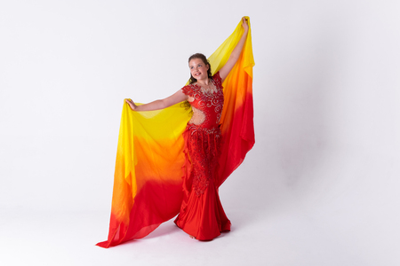 Young girl with shawl and in red dress performs oriental dance on white background.