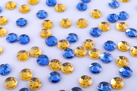 Many round yellow and blue sewn stones on a white background.
