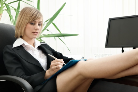 Businesswoman sitting with feet up on desk  Focus on face photo