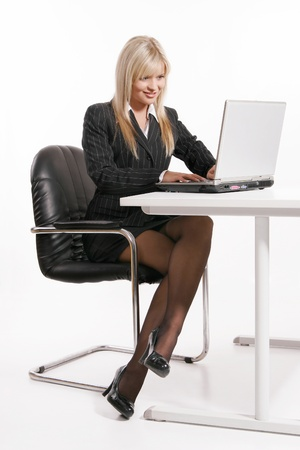 working attire: Young blonde woman working with laptop