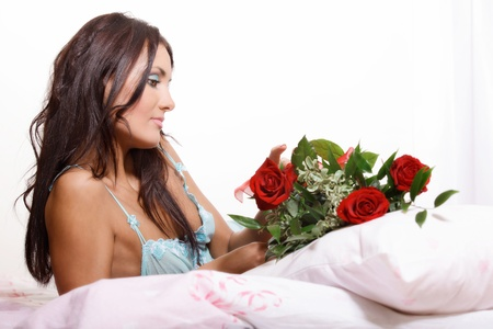 Beautiful sexy woman lying on bed in lingerie holding red roses  Selective focus photo