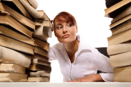 Beautiful young woman with stack of books on white background