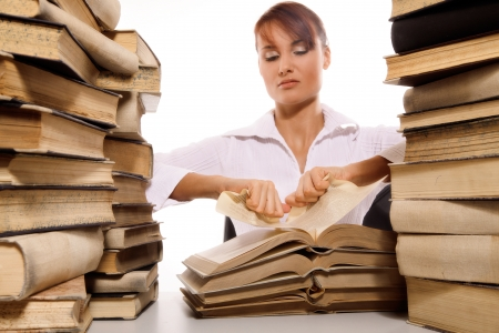 Beautiful young woman with stack of books on white background photo