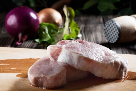 Raw pork chop on chopping board  Mysterious light Stock Photo