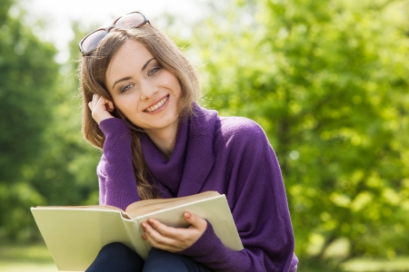 Beautiful girl reading a book and relax in the park Stock Photo
