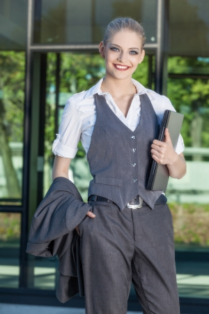 Smiling businesswoman standing at front of office building photo