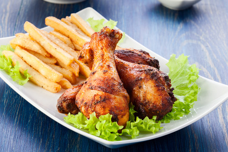 Chicken drumsticks with french fries  Selective focus