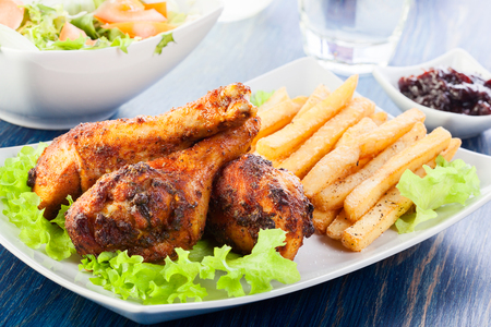 roast chicken: Chicken drumsticks with french fries  Selective focus