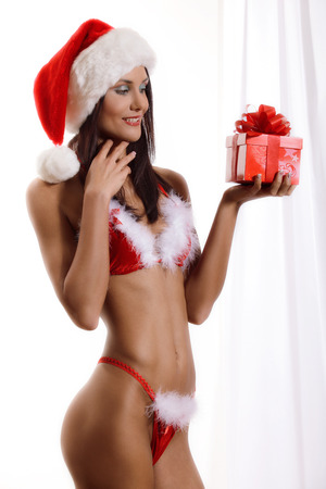 Sexy young Santa Girl with gift Stock Photo