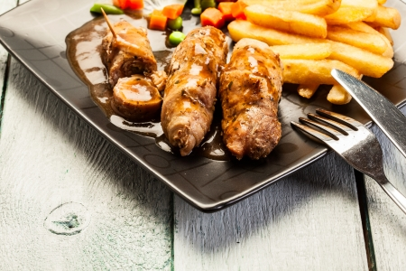 Beef rolls with french fries and begetables photo