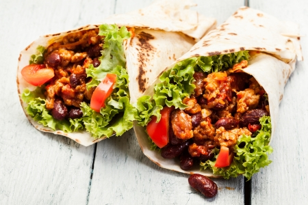 Burrito  Tortilla with meat and beans on a table  Stock Photo