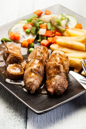 Beef rolls and vegetables on plate  photo