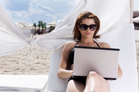 Pretty young woman with laptop on the beach photo