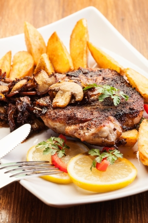 Fried pork chop with mushrooms and chips Stock Photo