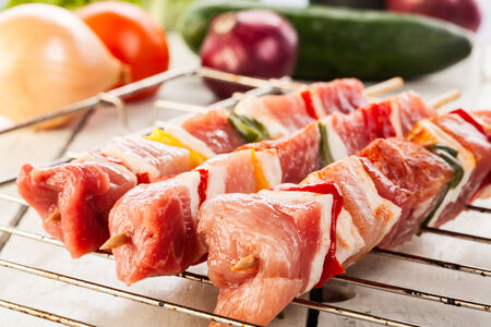 Raw shashlik and vegetables on grill