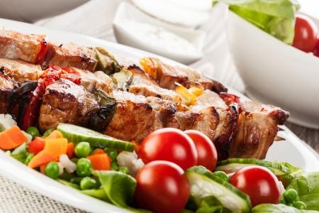 Grilled shashlik with vegetables on plate