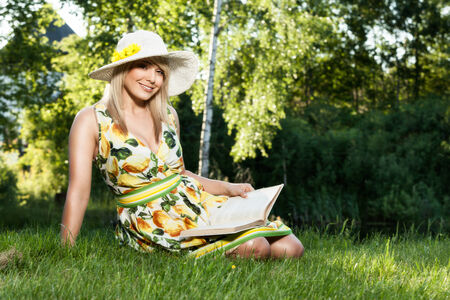 Blond beautiful woman reading book on a meadow Stock Photo