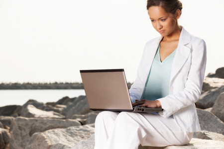 Young businesswoman on the beach with laptop photo