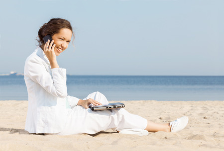 Young woman talking on cellphone on a beach  photo