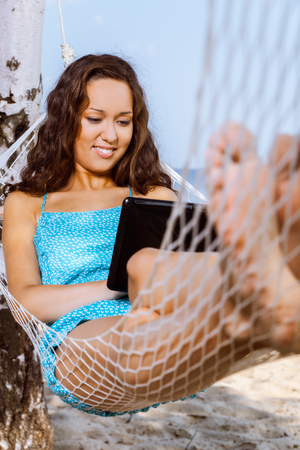 Young woman relaxing on hammock and using digital tablet photo