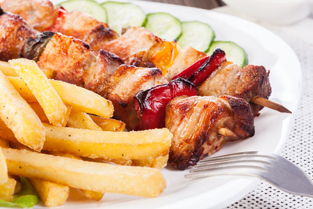 Grilled shashlik with chips on plate
