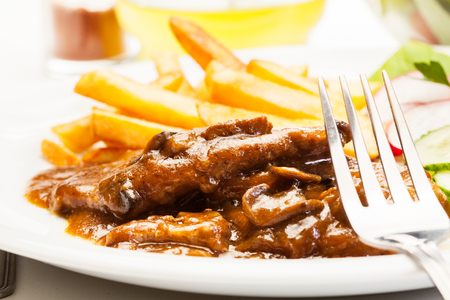 Pork chop with sauce, mushrooms and chips on a plate Stock Photo