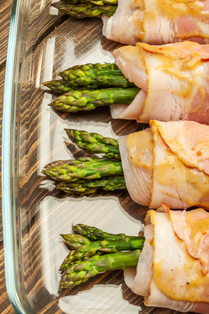 Fresh asparagus wrapped in chicken and bacon in a baking dish