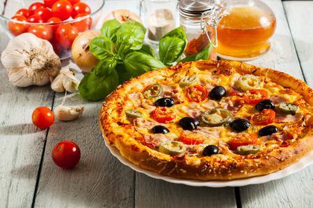 smack: Pizza with bacon, olives and jalapeno pepper on a plate Stock Photo