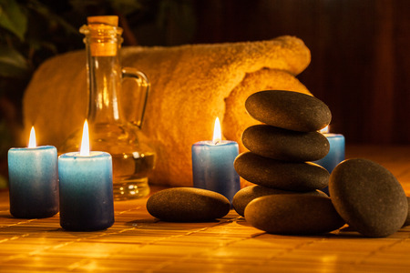 Spa still life with hot stones, essential oil and candles Stock Photo
