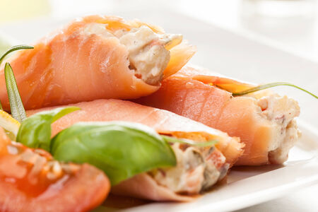 Smoked salmon roll with vegetable salad on a plate