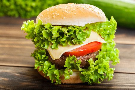Cheeseburger with lettuce, onions and tomato in a sesame bun on wooden table Stock Photo